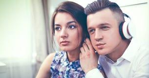 Glückliche junge Paare, die zusammen auf dem Boden sitzen Lizenzfreie Stockfotos