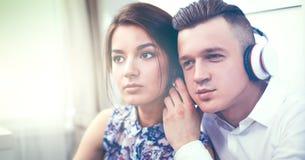 Glückliche junge Paare, die zusammen auf dem Boden sitzen Lizenzfreie Stockfotografie