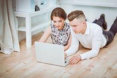 Glückliche junge Paare, die zusammen auf dem Boden sitzen Stockfotos