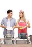 Glückliche junge Paare, die zusammen Platten und das Lächeln abwischen Stockbild