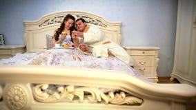 Glückliche junge Paare essen Frühstück im Bett tender stock video