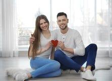 Glückliche junge Paare mit dem kleinen roten Herzen, das auf Boden sitzt Stockfotos