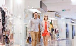 Glückliche junge Paare mit Einkaufstaschen im Mall Stockfoto