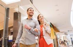 Glückliche junge Paare mit Einkaufstaschen im Mall Lizenzfreies Stockbild