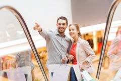 Glückliche junge Paare mit Einkaufstaschen im Mall Lizenzfreie Stockbilder