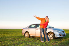 Glückliche junge Paare mit ihrem neuen Auto Lizenzfreie Stockfotografie