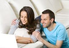 Glückliche junge Paare mit Laptop Lizenzfreie Stockfotos