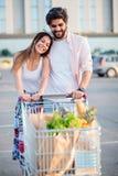 Glückliche junge Paare mit vollem Einkaufswagen vor dem Mall stockbilder