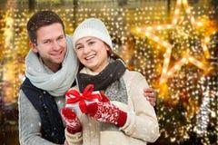 Glückliche junge Paare mit Weihnachtsgeschenk stockfotografie