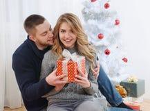 Glückliche junge Paare nähern sich Weihnachtsbaum mit Geschenk stockbilder
