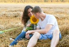 Glückliche junge Paare sitzen auf dem wheaten Gebiet am Abend, romantisches Leutekonzept, schöne Landschaft, Sommersaison Stockbild