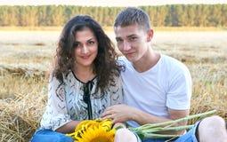 Glückliche junge Paare sitzen auf dem wheaten Gebiet am Abend, romantisches Leutekonzept, schöne Landschaft, Sommersaison Stockfoto