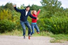 Glückliche junge Paare - springend in den Himmel Stockfotografie