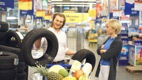 Glückliche junge Paare treffen Wahl mit Autoreifen im Einkaufszentrum stock video