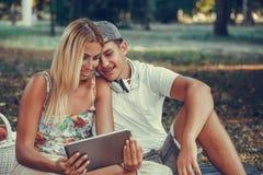 Glückliche junge Paare unter Verwendung der digitalen Tablette während des Picknicks im Park stockfotografie
