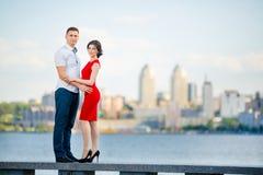 Glückliche junge Paarumarmungen gegen die Stadt Lizenzfreies Stockfoto