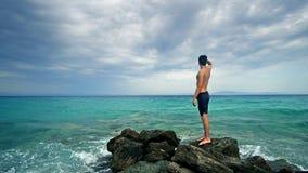 Glückliche Junge passten jugendlich Stellung auf Felsen und das Navigieren zum Horizont, der Ferien genießt Stockfoto
