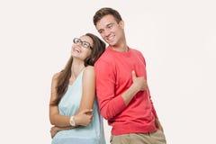 Glückliche junge reizende Paarstellung zurück zu Rückseite und Lachen über weißem Hintergrund Freundschaft und Verhältnisse lizenzfreie stockbilder