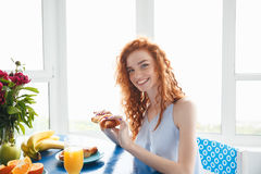 Glückliche junge Rothaarigedame, die am Tisch isst Hörnchen sitzt Stockfotos