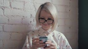 Glückliche junge Schönheit trinkendes coffe im Café und Simsen an ihrem intelligenten Telefon stock video footage