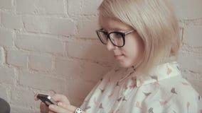 Glückliche junge Schönheit trinkendes coffe im Café und Simsen an ihrem intelligenten Telefon stock video