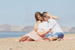Glückliche junge schwangere Familie in Meer Stockbild