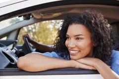 Glückliche junge schwarze Frau schaut aus einem Autofenster heraus Lizenzfreies Stockbild