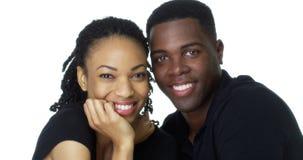 Glückliche junge schwarze Paare, die das Kameralächeln betrachten Lizenzfreies Stockbild