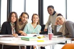 Glückliche junge Studenten bei Tisch, die zusammen studieren Stockfotografie