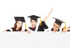 Glückliche junge Studenten im Aufbaustudium mit leerem Brett stockbild