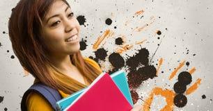 Glückliche junge Studentenfrau, die Notizbücher gegen grauen, gelben und schwarzen geplätscherten Hintergrund hält Lizenzfreie Stockfotografie