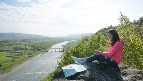 Glückliche junge touristische Frau, die auf den Felsen mit Kompass und Karte sitzt Illustration des Vektors EPS8 Stockfotos