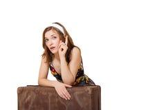 Glückliche junge touristische Frau, die mit Tasche und dem Zeigen sitzt Lizenzfreie Stockfotografie