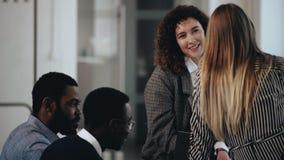 Glückliche junge verschiedene Geschäftsleute, die im modernen Dachbodenbüro sich treffen Schöne europäische lächelnde Frau, die m stock video