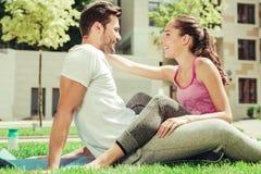 Glückliche junge weibliche Person, die nah an ihrem Partner sitzt stockbild