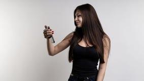 Glückliche junge zufällige Frau, die Mitteilungen an ihrem Telefon auf weißem Hintergrund liest lizenzfreie stockbilder