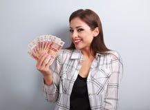 Glückliche junge zufällige Frau, die Rubel mit dem toothy Lächeln auf b hält Lizenzfreie Stockbilder