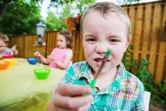 Glückliche Jungen-Haltungen mit einem Pinsel Lizenzfreie Stockbilder