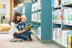 Glückliche Jungen-und Lehrer-Reading Book In-Bibliothek lizenzfreie stockbilder