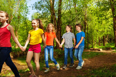 Glückliche Jungen und Mädchen, die in den Sommerwald gehen Stockfoto
