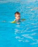 Glückliche Jungenschwimmen mit floaties lizenzfreie stockfotos