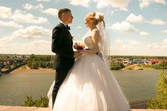 Glückliche Jungvermählten, Braut und Bräutigam, die auf Fluss mit schönen Ansichten aufwirft Lizenzfreie Stockfotografie
