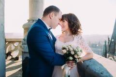 Glückliche Jungvermählten, die durch Stirnen auf dem Balkon der alten gotischen Kathedrale sich berühren Stockfotografie