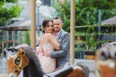 Glückliche Jungvermählten, die nahe dem Karussell huging sind stockbild