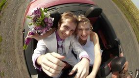Glückliche Jungvermählten in einem Auto stock video footage