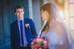 Glückliche Jungvermählten gegen ein blaues modernes Gebäude lizenzfreie stockfotografie