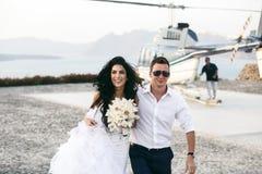 Glückliche Jungvermählten nahe dem Hubschrauber stockfotos