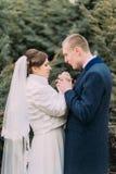 Glückliche Jungvermähltenpaare, zarte Braut und mildern Bräutigam, Händchenhalten zusammen beim Gehen in grünen Park Stockfoto