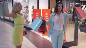 Glückliche Käuferfreundinnen tanzen nachdem, kaufend an den Rabatten in teure Speicher in den Verkäufen, würzen am Mall, Text stock footage