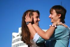 Glückliche küssende Paare nähern sich neuem weißem Gebäude Lizenzfreie Stockfotos
